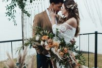 a dreamy boho fall wedding arch with lots of greenery and foliage, blush, rust blooms and berries, eucalyptus and pampas grass