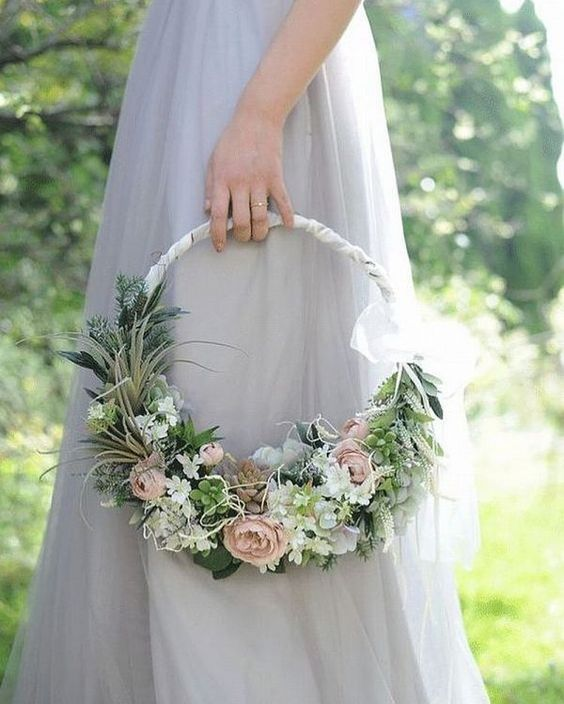 a dreamy hoop wedding bouquet of pale and pastel blooms, greenery, succulentsand a ribbon wrap on top is a chic idea