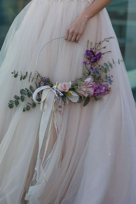 a dreamy hoop wedding bouquet with blush and purple blooms and eucalyptus and bows of long ribbons is a chic idea
