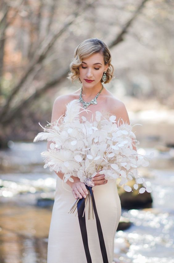 a dreamy lunaria and feather wedding bouquet with a vintage brooch and black ribbons is a lovely idea for a refined bridal look