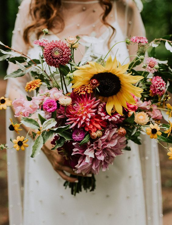 a dreamy summer wedding bouquet with pink, blush, orange blooms and sunflowers plus some foliage is a cool idea for a relaxed summer bride