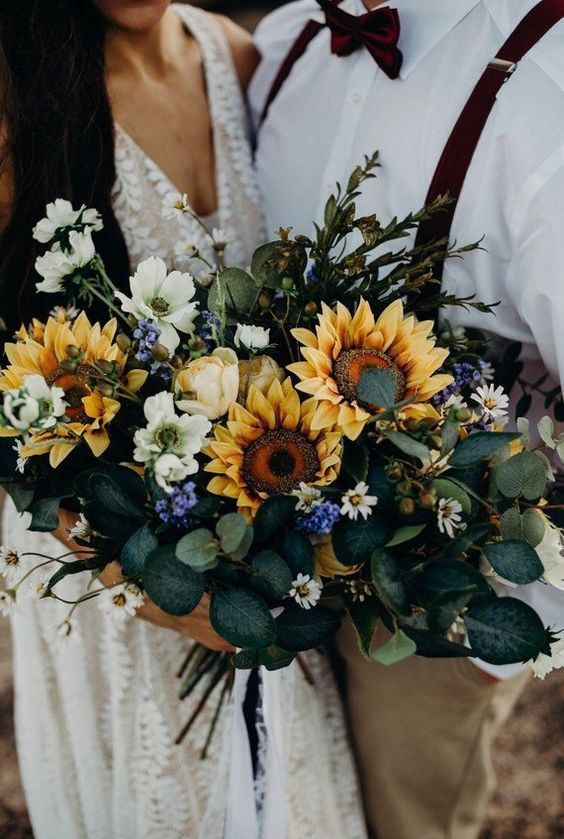 a dreamy sunflower wedding bouquet with eucalyptus, sunflowers, white and blue blooms and herbs is amazing