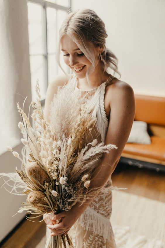 a dried boho wedding bouquet with bunny tails, pampas grass, proteas and dried foliage is a chic idea for a summer or fall wedding