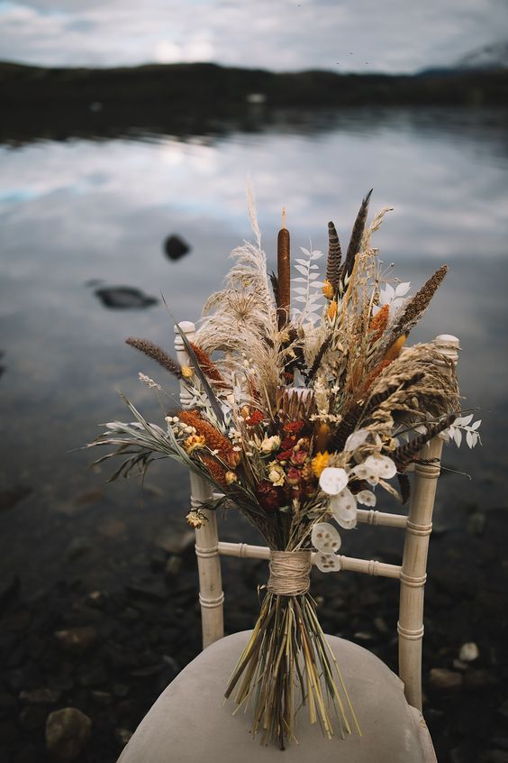 a dried fall wedding bouquet with lunaria, astilbe, feathers, proteas, daises and bunny tails, grasses and greenery for a fall boho wedding