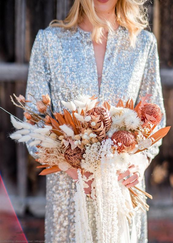 a dried flower wedding bouquet with bunny tails, colorful dried king proteas, billy balls, fronds and leaves plus creative ribbons