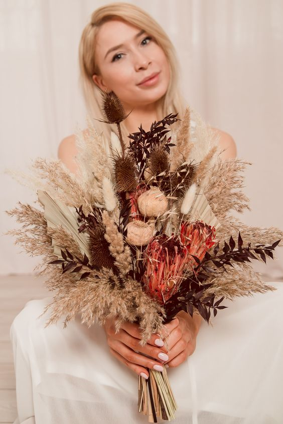 a dried flower wedding bouquet with dried peonies, astilbe and thistles, king proteas, fronds, dark foliage and grasses is a cool idea for the fall