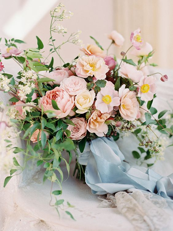 a fab wedding bouquet of pink roses and peonies, white and dusty pink blooms, greenery and blue ribbons is wow