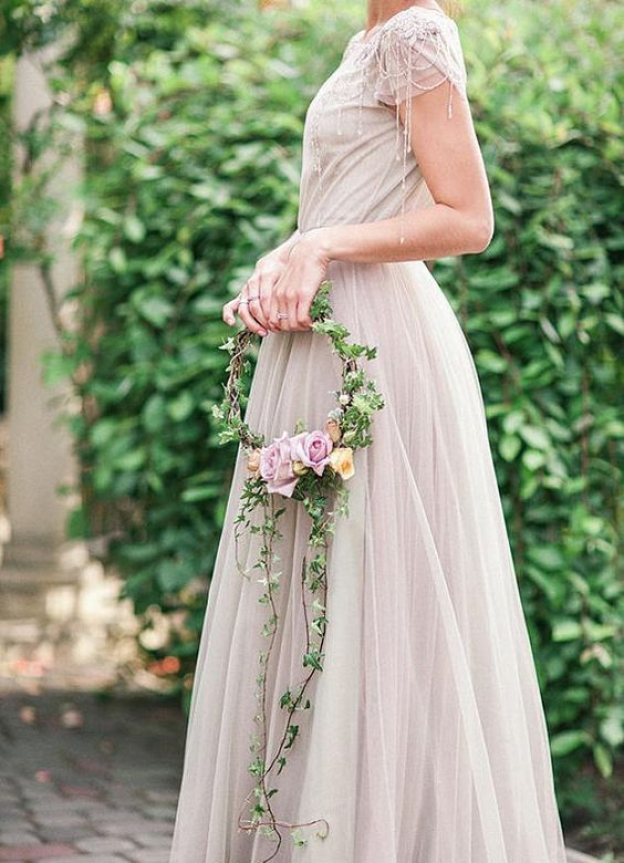 a fairy-tale hoop wedding bouquet with lots of greenery, peachy and pink roses is a very chic and cool idea for a fairy-tale wedding