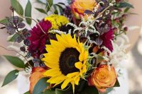 a fantastic and bold fall wedding bouquet of purple and yellow roses, sunflowers, dark foliage and greenery plus berries