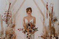 a fantastic boho fall wedding arch shaped as a house, with pampas grass, blush blooms, bold dried leaves is amazing