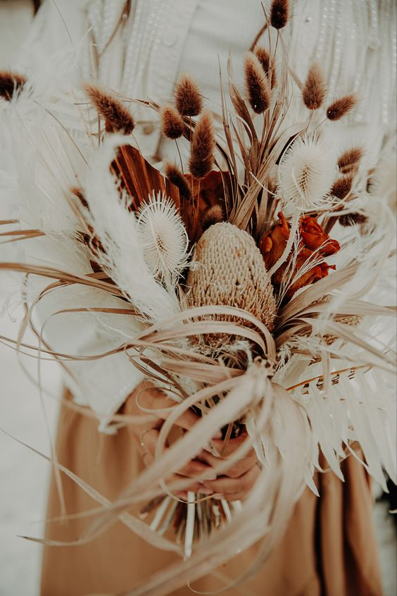 a fantastic boho wedding bouquet with bunny tails, proteas, dried air plants and spray painted fronds is a lovely idea for summer or fall