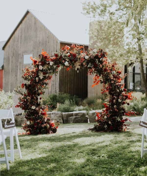 a fantastic round fall wedding arch with blush, burgundy and red blooms, greenery and colorful fall leaves and foliage is amazing