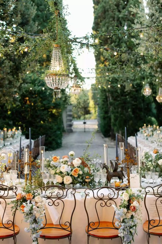 a fantastic secret garden wedding tablescape done in rust and peachy tones, with tall white and navy candles, refined blooms and chic linens