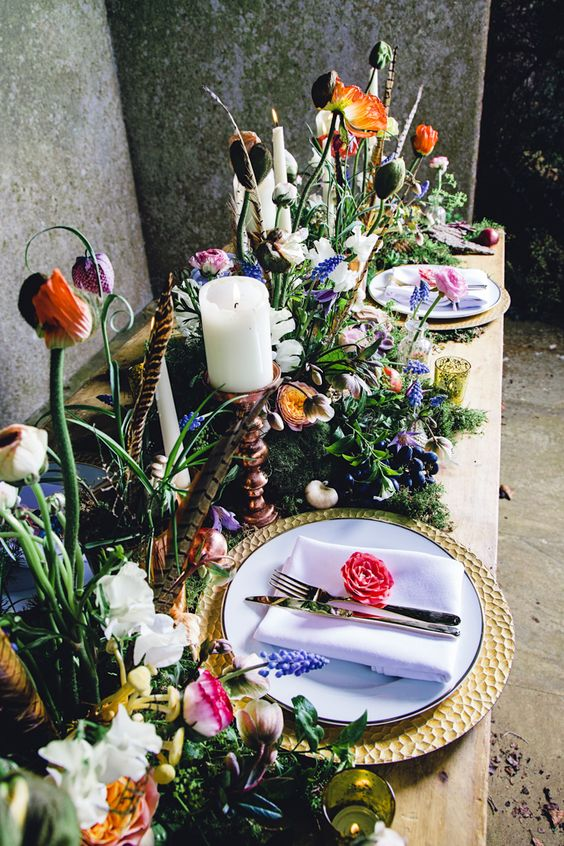 a gorgeous and colorful secret garden wedding tablescape with a moss runner, feathers, candles, gold chargers and neutral linens
