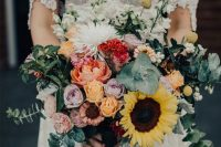 a gorgeous and colorful wedding bouquet of yellow and lilac roses, red and pink blooms, sunflowers, billy balls, white flowers and greenery