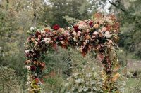 a gorgeous rustic fall wedding arch decorated with greenery and dried foliage, with bold and pastel blooms on top is very lush and eye-catchy