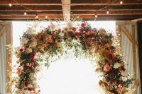 a gorgeous rustic fall wedding arch done with lots of greenery, pampas grass, blush, deep red, burgundy blooms and candle lanterns