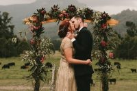 a gorgeous rustic fall wedding arch with greenery, pink king proteas, deep purple blooms is a very stylish and elegant idea