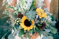 a gorgeous rustic wedding bouquet with eucalyptus, sunflowers, a succulent, white blooms and billy balls for a rustic bride