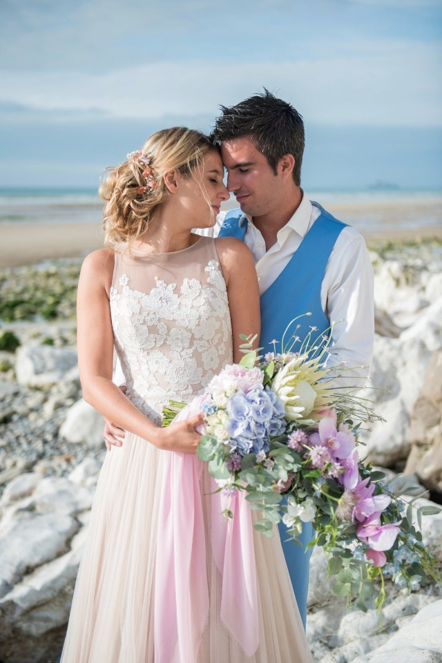 a groom wearing a blue suit with a waistcoat and a bride holding a blue and pink cascading wedding bouquet with greenery