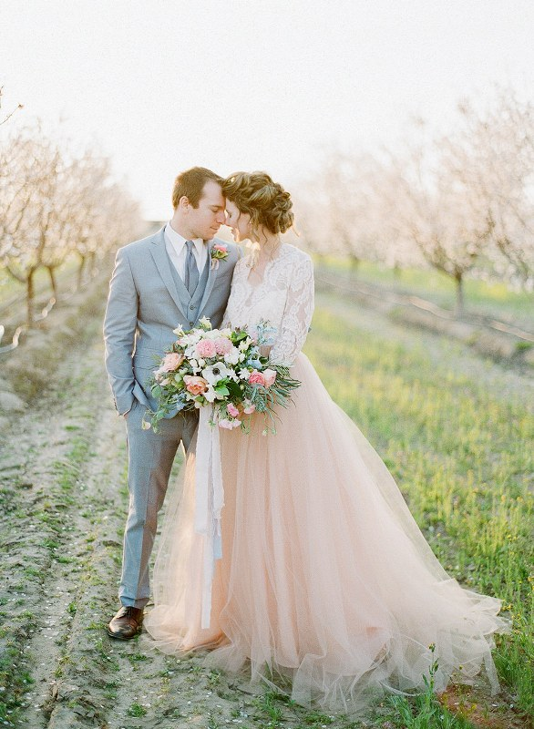 a groom wearing a blue three-piece suit, a bride wearing a white lace top and a blush tulle skirt with a train plus a blue and pink wedding bouquet