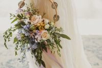 a hoop wedding bouquet with lush greenery and pastel blooms with plenty of texture and dimension is a lovely idea