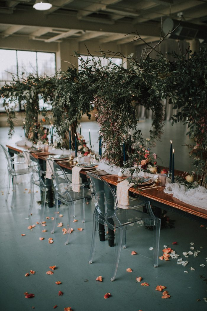 a jaw-dropping indoor secret garden wedding tablescape with a lush centerpiece over it, navy candles, neutral linens and bold blooms