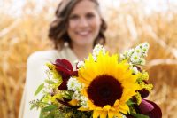 a lovely fall wedding bouquet with purple blooms and foliage, greenery, sunflowers and daises is a cool idea for a rustic or boho bride