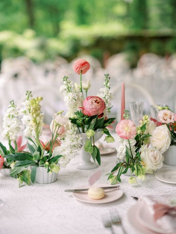 a lovely pastel secret garden wedding tablescape with neutral and pink blooms and greenery, a lace tablecloth and pink candles is a chic idea