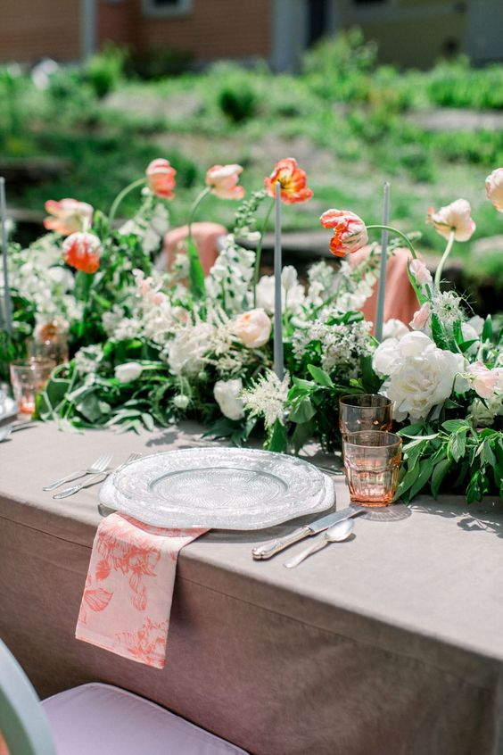a lovely secret garden wedding tablescape with muted and printed linens, a lush greenery and bold floral runner plus tall candles