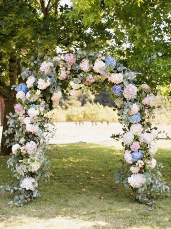 a lovely wedding arch covered with eucalyptus, white, blue and pink hydrangeas is an amazing idea for a spring or summer wedding