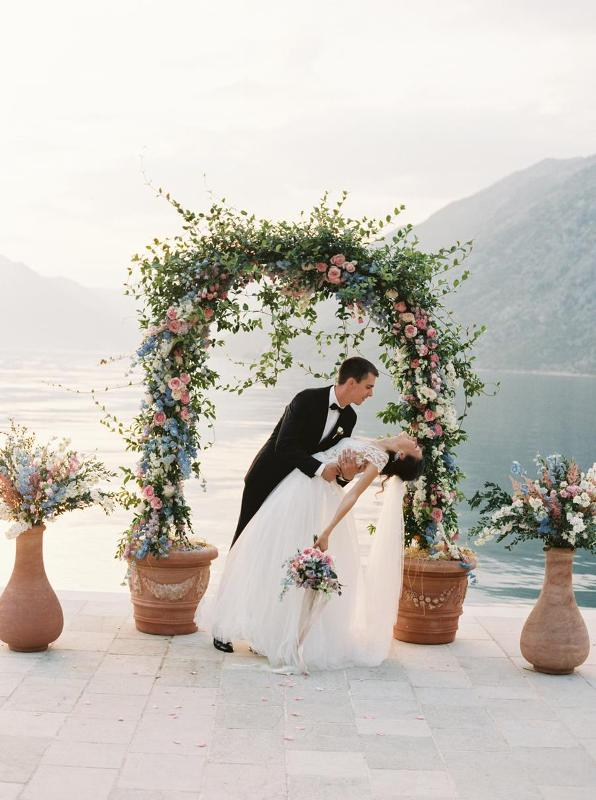 a lovely wedding arch made of greenery, pink, white and blue flowers and matching arrangements around is a gorgeous idea