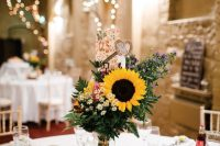 a lovely wedding centerpiece with wildflowers, fern and a sunflower, thistles, a burlap heart placed on a wood slice is a gorgeous idea