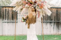 a lush and bold boho fall wedding arch with pampas grass and bold blooms plus macrame hanging down is amazing