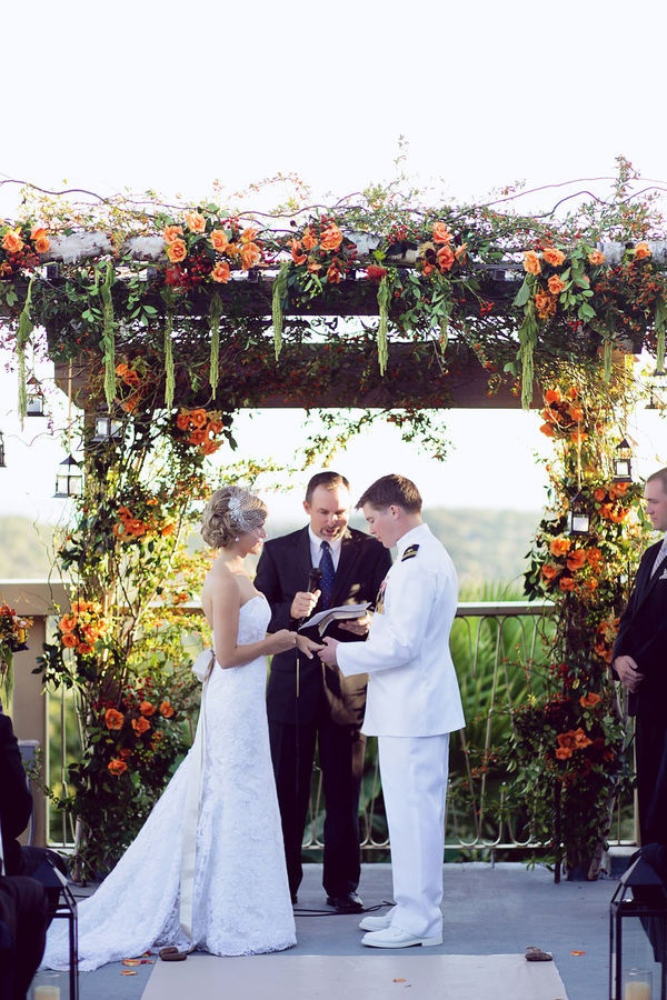 a lush fall rustic wedding arch with lots of greenery, orange, red blooms and berries and lots of twigs and cascading details is amazing