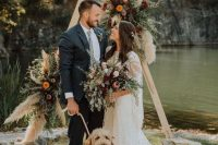 a lush triangle boho fall wedding arch with greenery, pampas grass, pink, orange and burgundy blooms is very cool