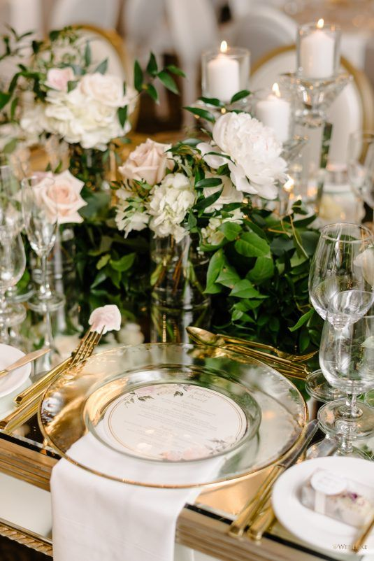a luxurious secret garden wedding tablescape with a mirror tablescape, sheer plates, blush and white roses and greenery plus candles