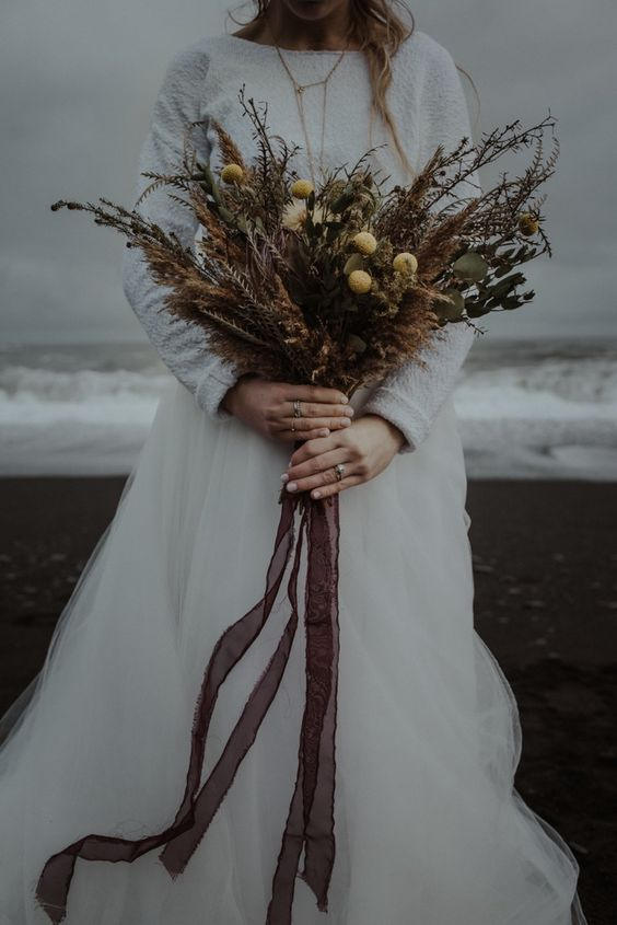 a moody fall or winter wedding bouquet of billy balls, eucalyptus, dried grasses and dried blooms plus long ribbons is a cool idea