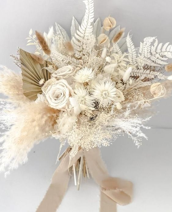 a neutral dried flower wedding bouquet with ferns, daisies, fronds, bunny tails, seed pods and pampas grass plus tan ribbons