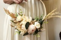 a neutral hoop wedding bouquet with neutral and pastel blooms, greenery and wheat is a lovely and delicate idea for a bride or bridesmaid