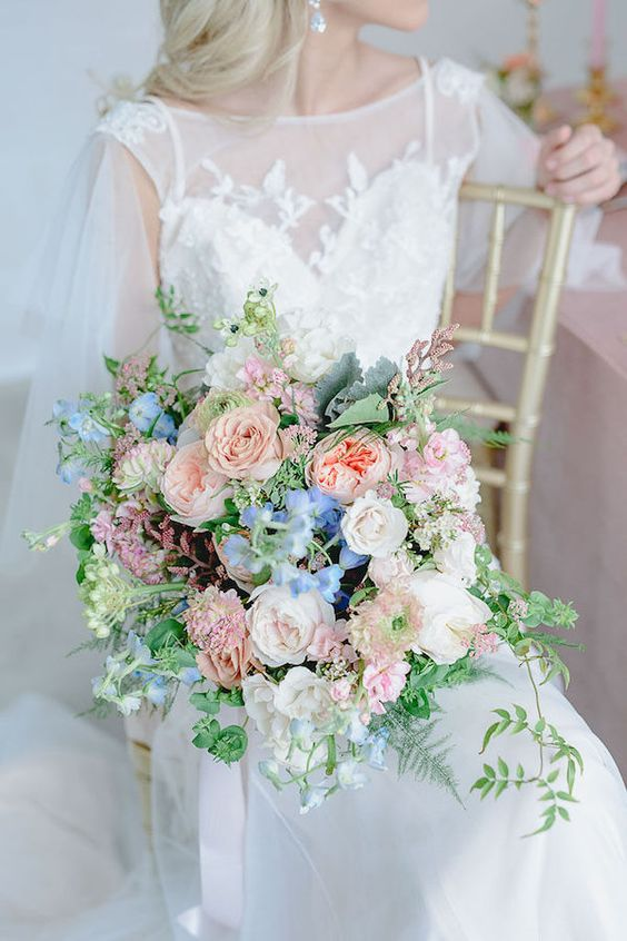 a pastel wedding bouquet of blush, dusty pink and peachy pink plus blue flowers and greenery is amazing for spring