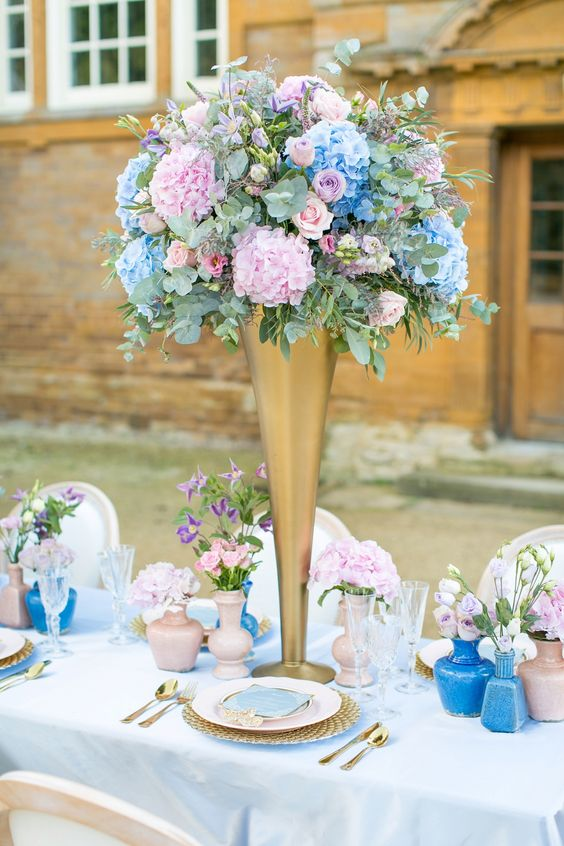 a pastel wedding tablescape with blue and pink vases, blush plates, tall pink and blue floral centerpieces and gold cutlery and chargers