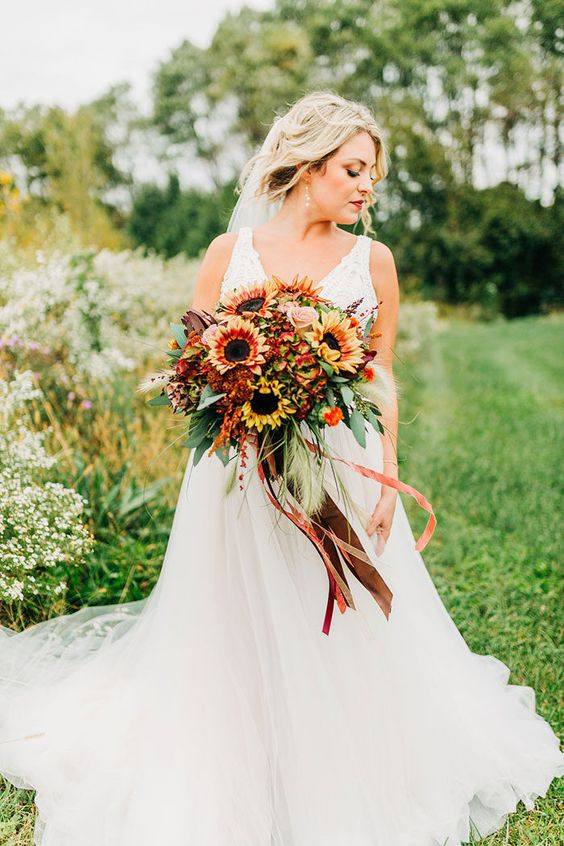 a pretty and bold fall wedding bouquet of sunflowers, roses, greenery, feathers and with long and bold ribbons is wow
