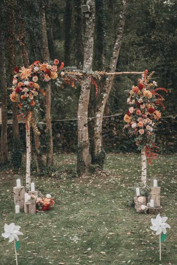 a pretty and bright rustic fall wedding arch of birch branches, rust, blush, burgundy, orange and red blooms, some eucalyptus, candle lanterns