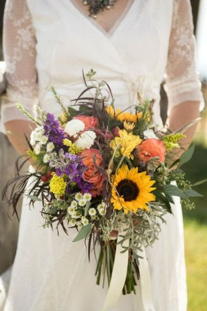 a pretty and colorful summer wedding bouquet with much textural greenery, sunflowers, pink, purple and yellow blooms is a lovely idea