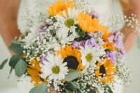 a pretty and relaxed summer wedding bouquet of sunflowers, white and purple blooms, baby's breath and eucalyptus
