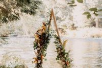 a pretty boho fall triangle wedding arch done with greenery, rust, blush and pink blooms, dried grasses and leaves