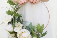 a pretty hoop wedding bouquet with lush white blooms and leaves is a chic idea for a spring wedding, and silk flowers won't wither