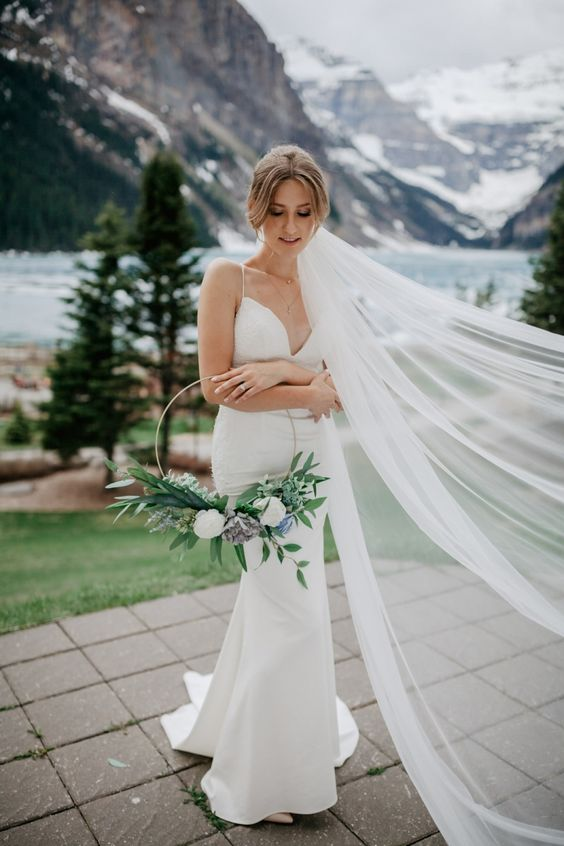 a pretty hoop wedding bouquet with white and blue blooms and lots of greenery is a stylish idea for a spring bride