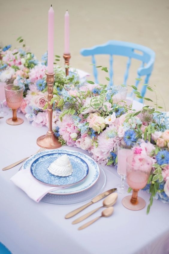 a pretty pink and blue wedding tablescape with a pink tablecloth, a pink and blue floral runner, pink candles and glasses, pink printed plates